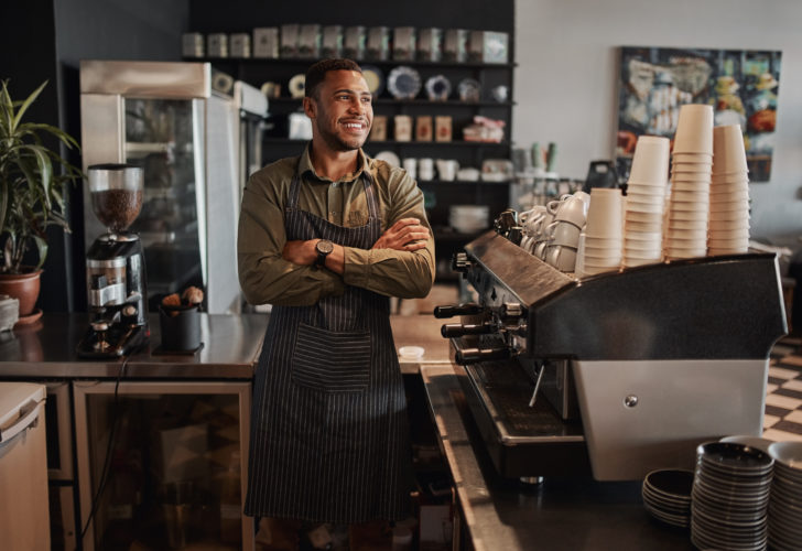 Successful handsome male cafe owner daydreaming standing with arms crossed looking away